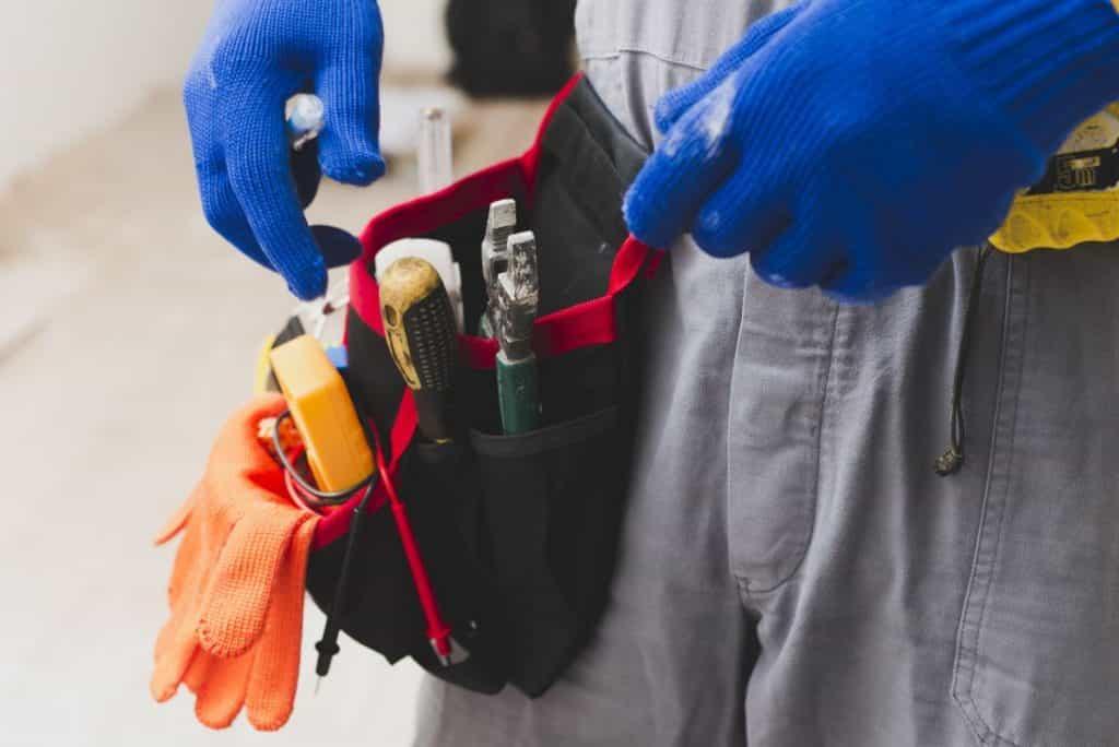 腰道具に手を伸ばす電気工事士