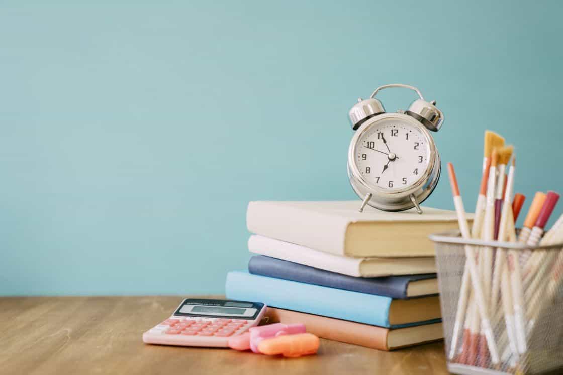 時計と積み重なった本