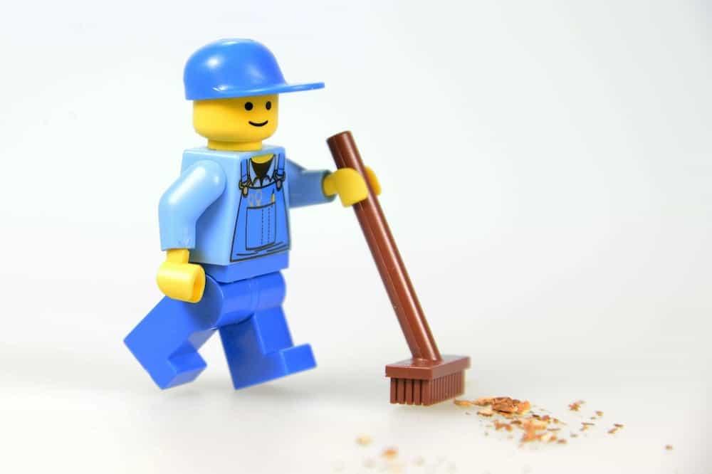 箒で床のゴミを掃いている人