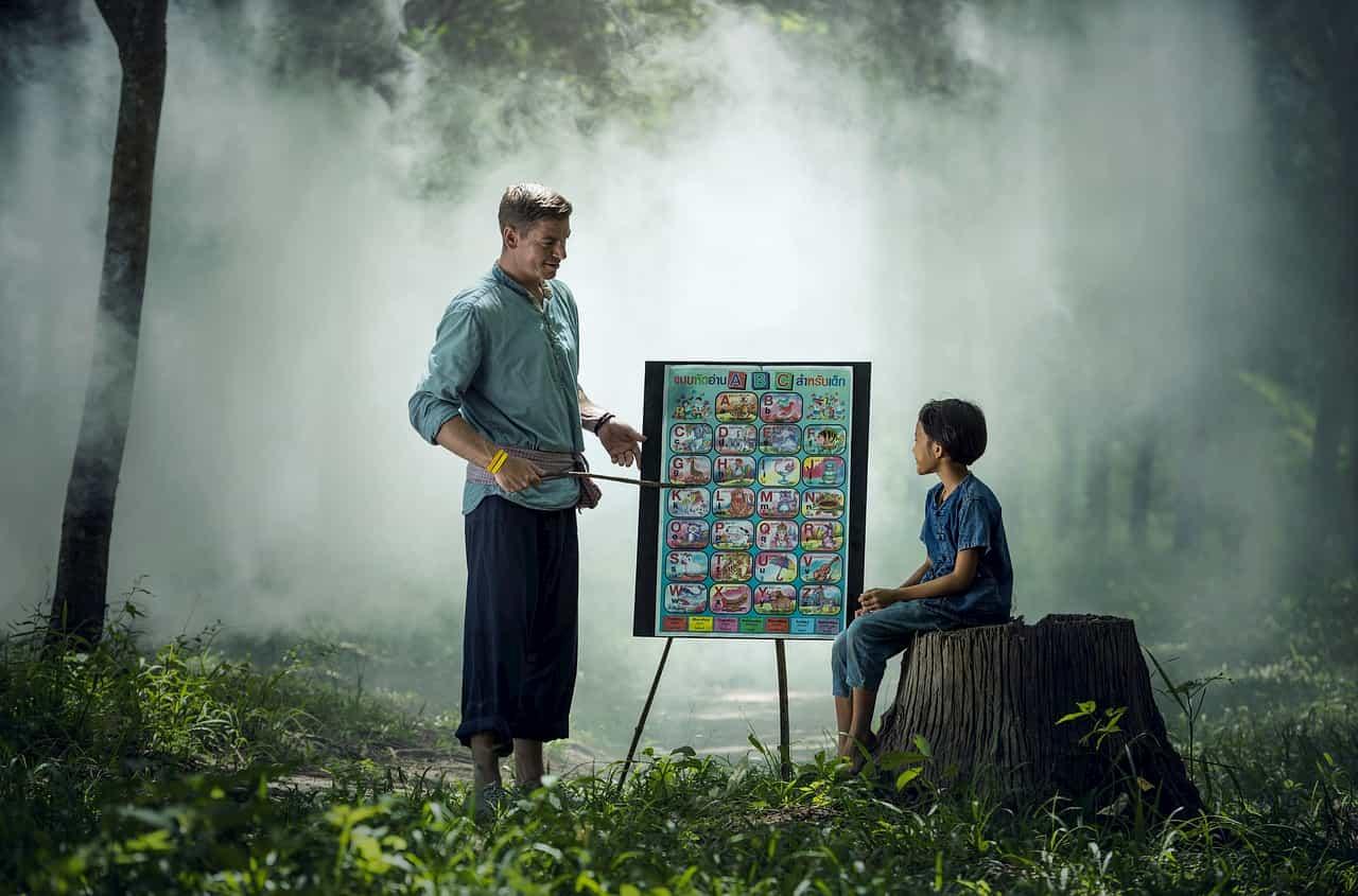 森で授業をする先生と生徒