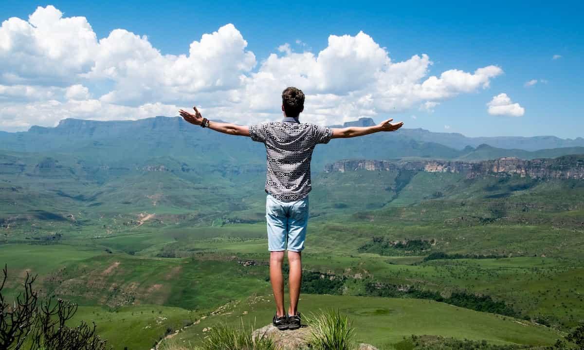 山頂で手を伸ばす人