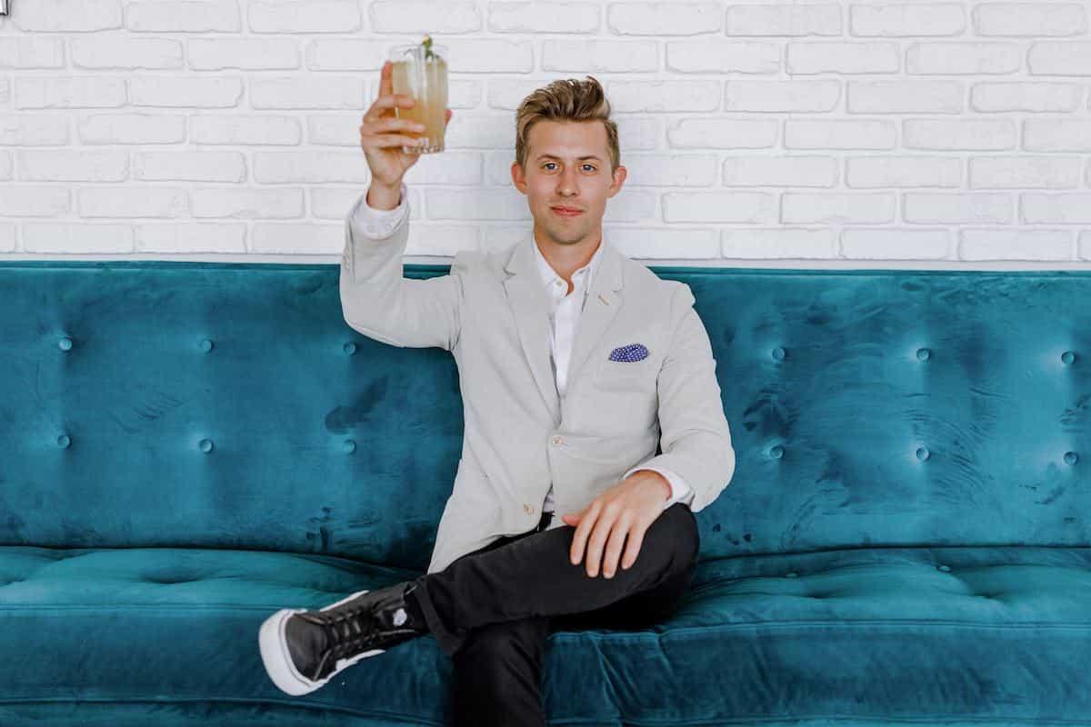 ソファに座り、飲み物をかざす男性